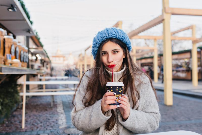 Cute dark-haired girl with sparkle manicure drinking tea on the street during winter photoshoot. Shy brunette young lady stock image