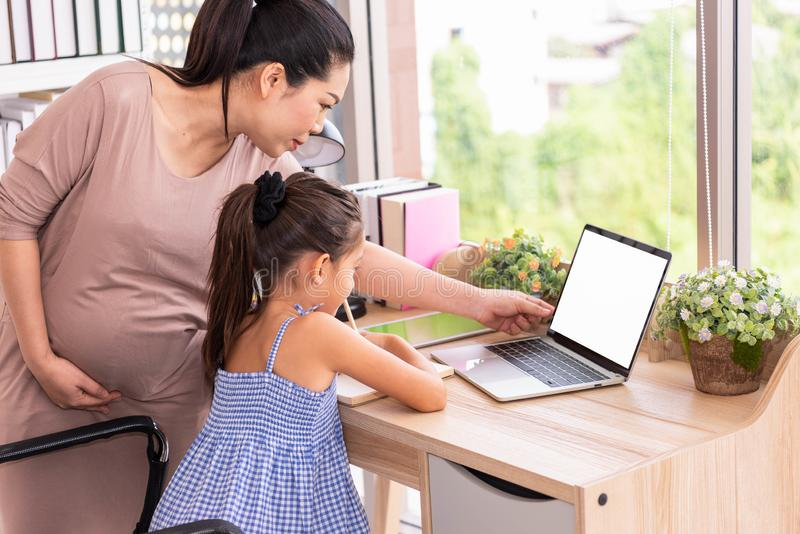 Cute daughter and her pregnant mother using white blank screen laptop at home. Parenthood and technology. Health and medical. royalty free stock image