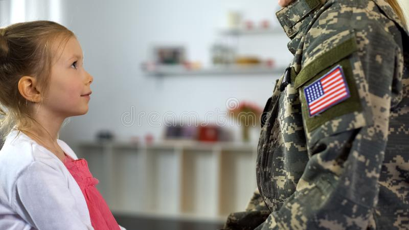 Cute daughter looking with love at mother in military form, happy homecoming royalty free stock images