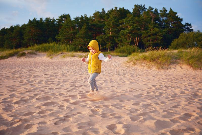 Delighted baby boy having fun, running on the sandy autumn beach near the pine tree forest stock images