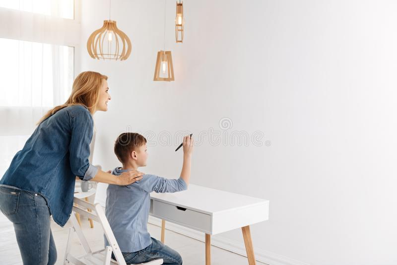 Cute delighted boy using progressive technology. Digital innovations. Cute happy delighted boy sitting at the table and drawing on a virtual screen while using royalty free stock photography
