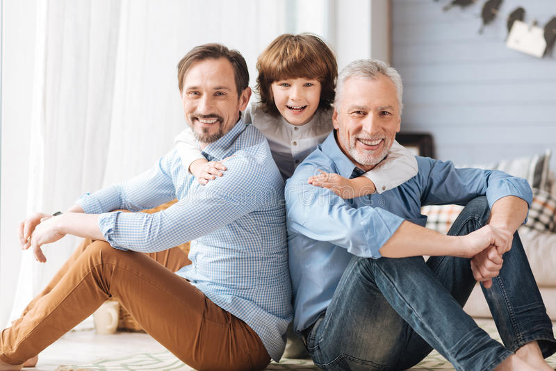 Cute delighted child hugging his father and grandfather royalty free stock image