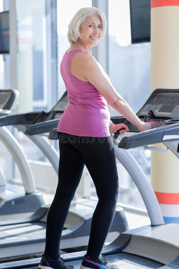 Cute delighted senior woman exercising on treadmill. royalty free stock images
