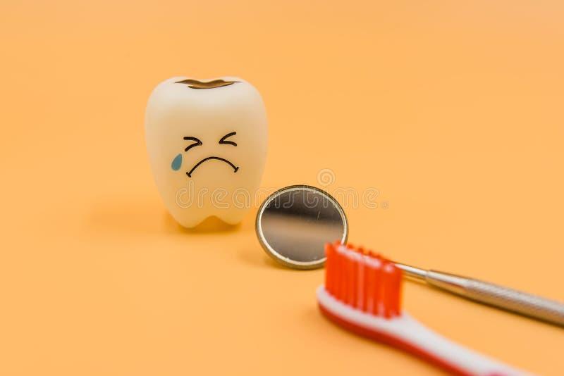 Cute di modello gioca i denti in odontoiatria su un fondo giallo immagine stock