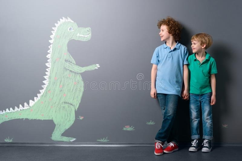Cute dinosaur and two boys. Smiling green dinosaur is coming to happy friends holding each other`s hands royalty free stock photography