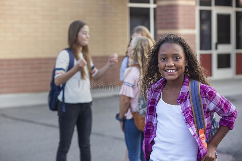 Cute, diverse pre-adolescent teen student hanging out with friends after school. Selective focus on the smiling girl student stand royalty free stock photo