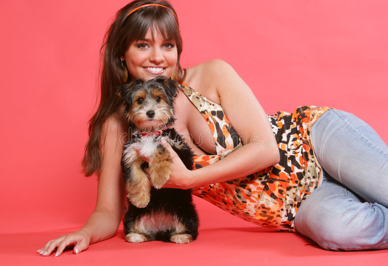 Cute Dog #2. A cute and young woman loving and playing with her dog isolated in a red background stock images