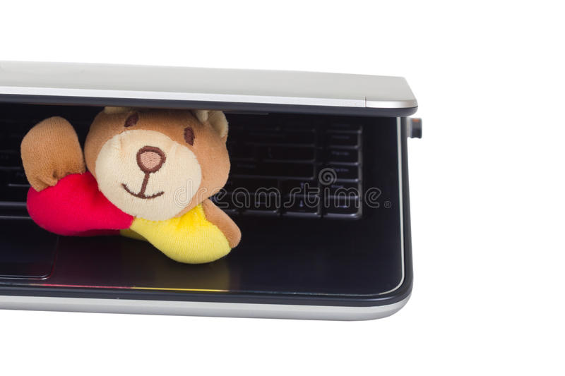 A cute doll toy hiding under laptop.