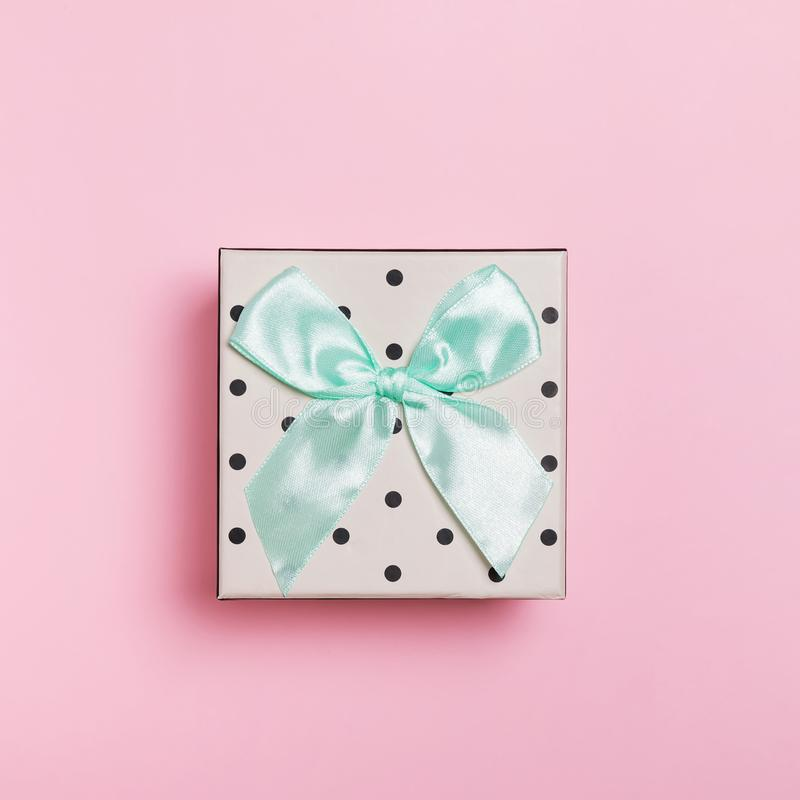 Cute dotted gift box on pastel pink background, top view. stock photography