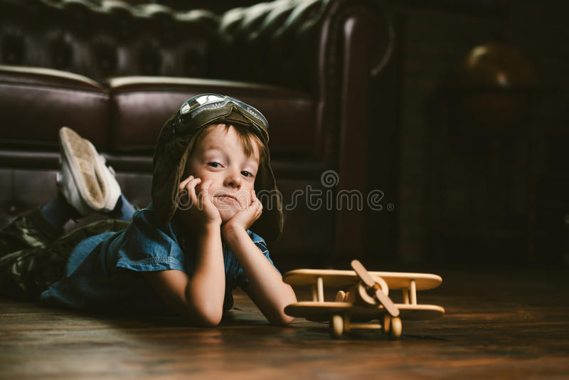 Cute dreamer boy. Playing with toy airplane at home. Childhood. Fantasy, imagination royalty free stock photos