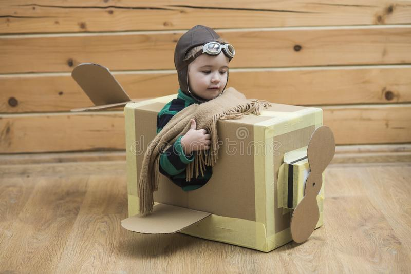 Brave dreamer boy playing with a cardboard airplane. Cute dreamer boy playing with a cardboard airplane. Childhood. Fantasy, imagination. Retro style royalty free stock photo