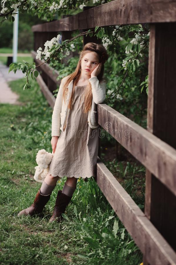 Cute dreamy child girl posing at rustic wooden fence with teddy bear. And blooming cherry on background stock image