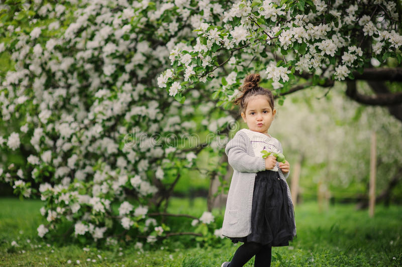 Cute dreamy toddler child girl walking in blooming spring garden. Celebrating easter outdoor royalty free stock photography