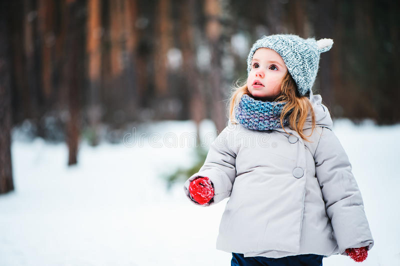Cute dreamy toddler girl walking in winter forest. In grey coat and hat stock photos