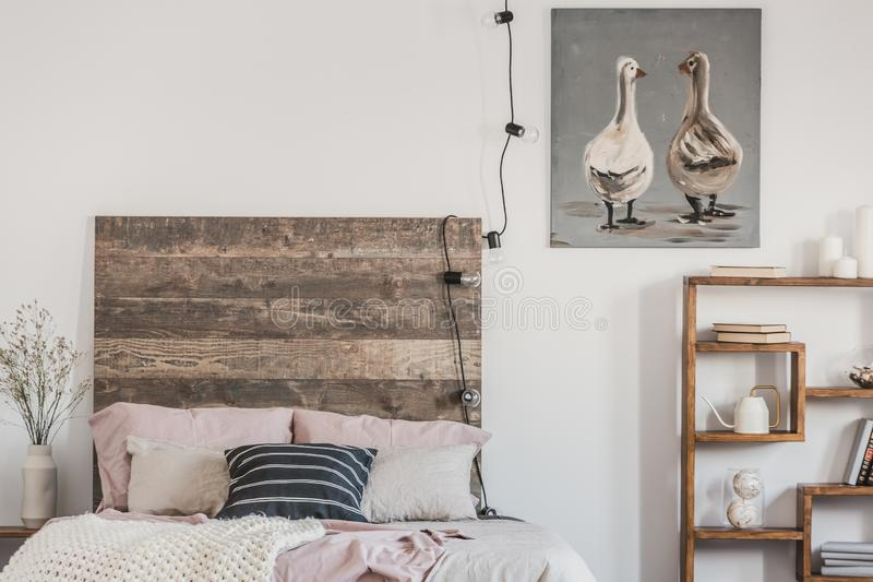 Cute ducks on grey oil painting in white rustic bedroom interior with fancy bookshelf and bed with wooden headboard. Cute ducks on grey oil painting in white royalty free stock image