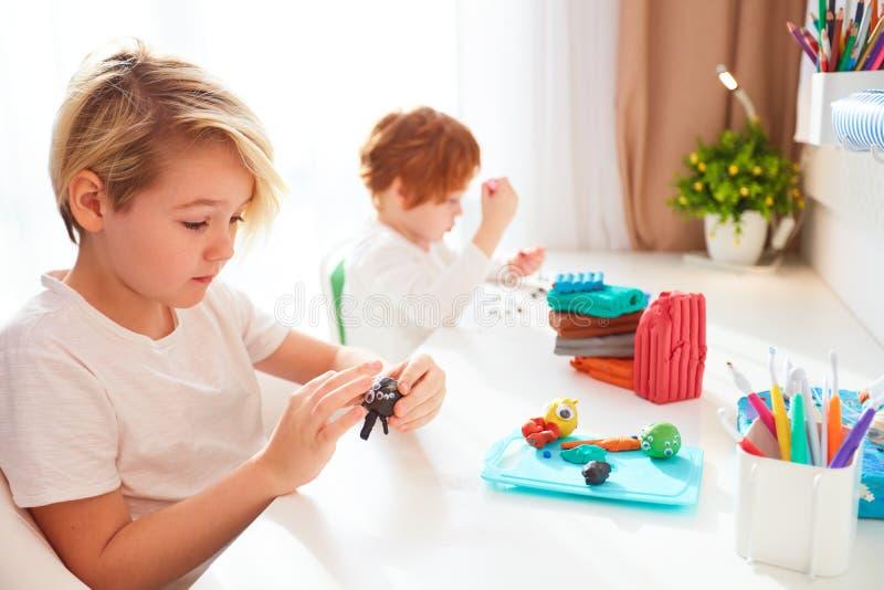 Cute dzieciaki tworzą ręczne rzemiosła z modelowania plastyny w pokoju dla dzieci zdjęcie royalty free