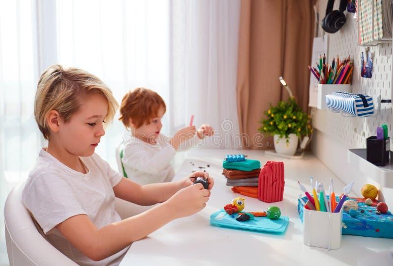 Cute dzieciaki tworzą ręczne rzemiosła z modelowania plastyny w pokoju dla dzieci obrazy stock