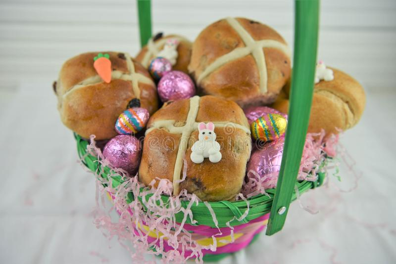 Cute Easter basket filled with fresh hot cross buns and easter eggs stock photos