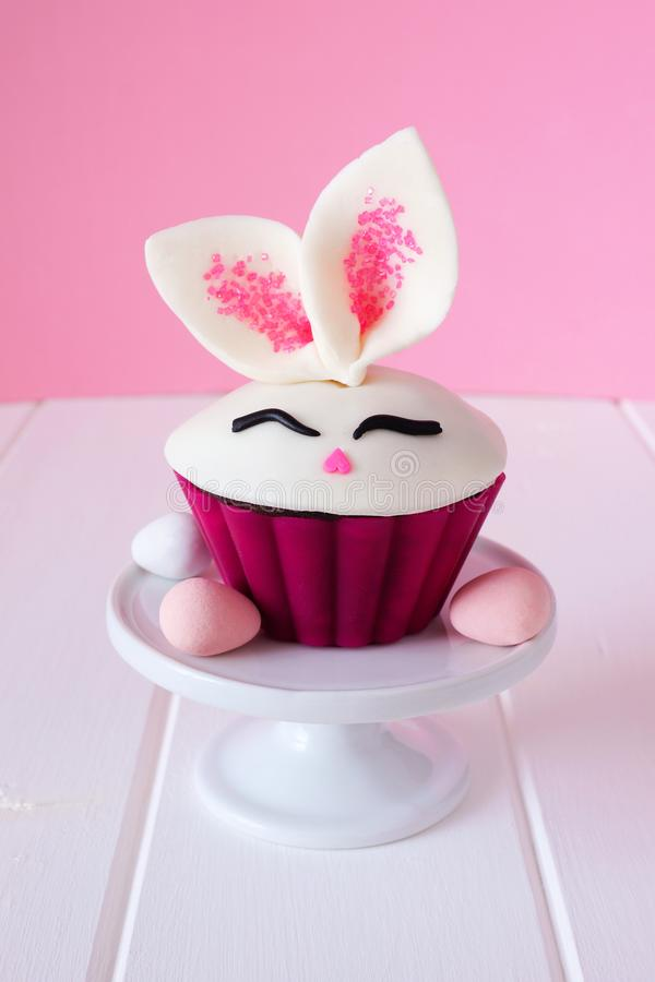 Easter bunny cupcake on a stand, close up with a pink background royalty free stock photo