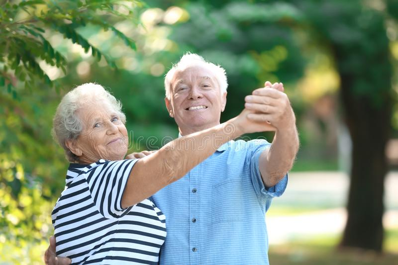 Cute elderly couple dancing outdoors. stock image