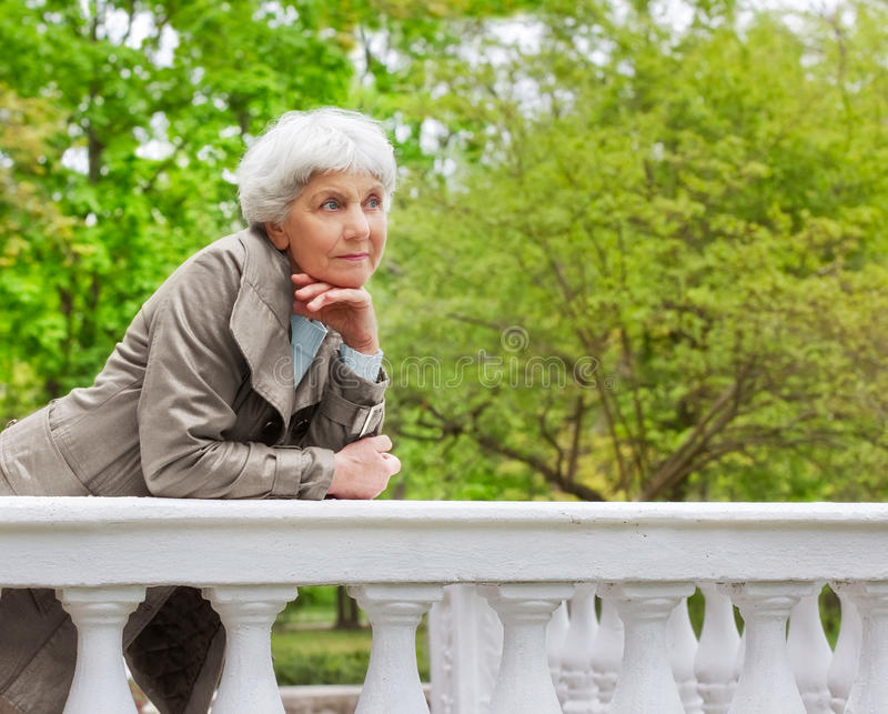 Cute elderly woman senior on the beautiful white verandah n the park stock photography