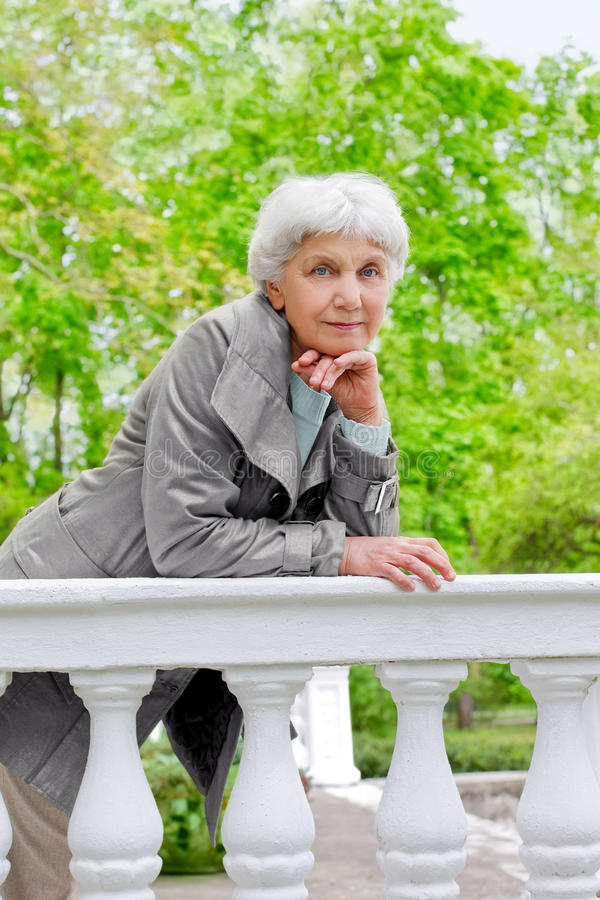 Cute elderly woman senior on the beautiful white verandah royalty free stock image