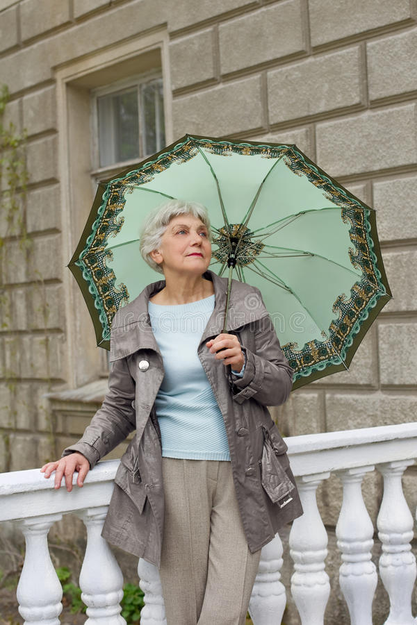 Cute elderly woman senior with an umbrella on the beautiful white verandah stock image
