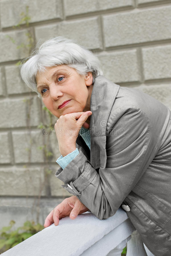 Cute elderly woman senior on the verandah royalty free stock photo