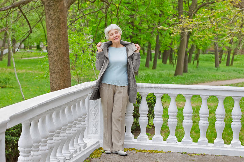 Cute elderly woman senior on the verandah in the park stock photography