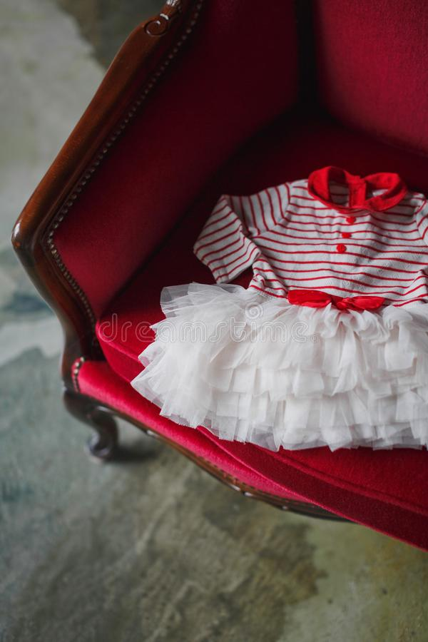 A pretty dress for a little girl lies on a red luxurious sofa. stock photos