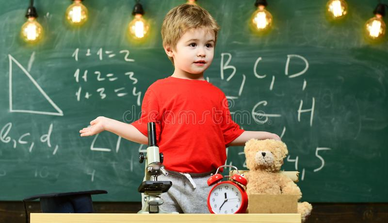 Cute elementary school boy with microscope at his desk at home. Young scientist making experiments in his home stock photography