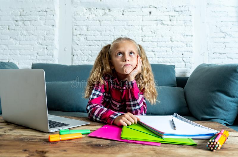 Cute elementary student feeling sad and confusing while doing difficult assignment with her laptop at home in primary school. Homework and children education royalty free stock photography