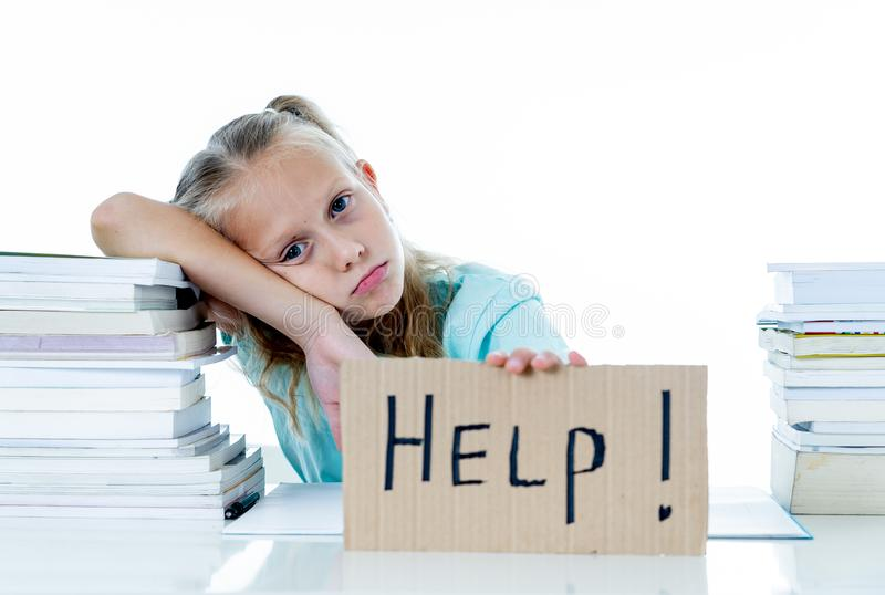 Cute elementary student feeling sad and confusing with too many schoolbooks at home in primary school royalty free stock photos