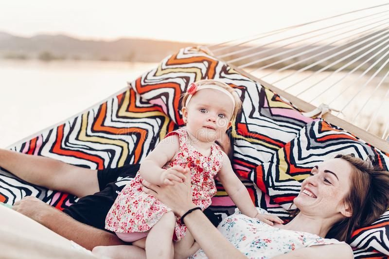 Cute, emotional baby girl in pretty dress with her mother and father in a hammock on vacation, funny baby face at sunset lake stock photo