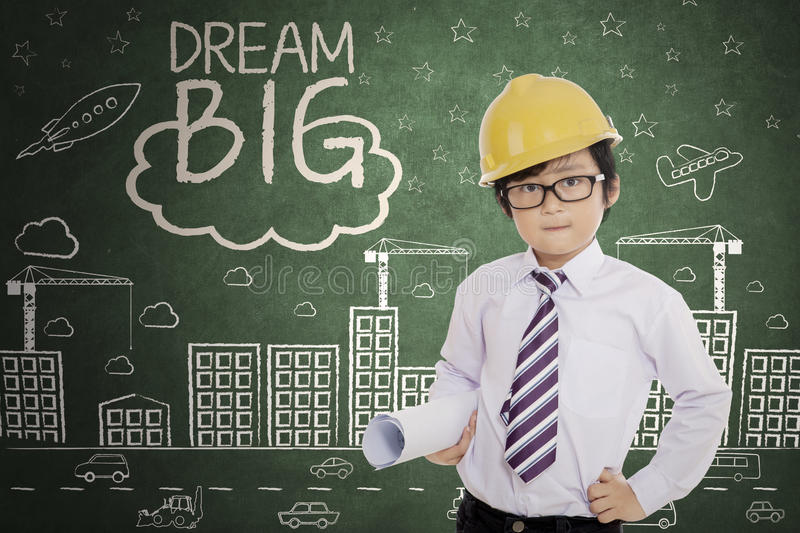 Cute engineer with text of dream big. Cute little engineer holding a blueprint while standing with text of dream big and scribbles on the chalkboard royalty free stock images