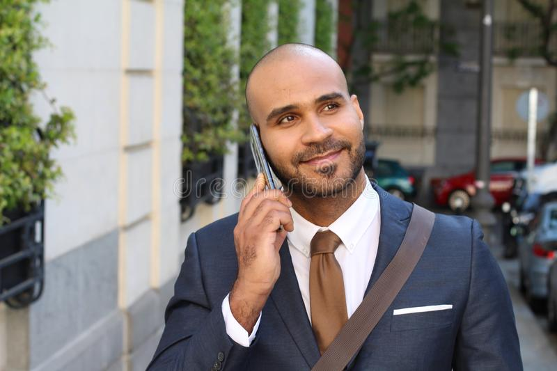 Cute ethnic businessman calling by phone outdoors royalty free stock photography