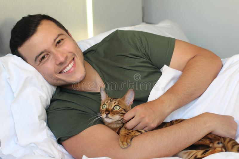 Cute ethnic man sleeping with his cat.  royalty free stock photography