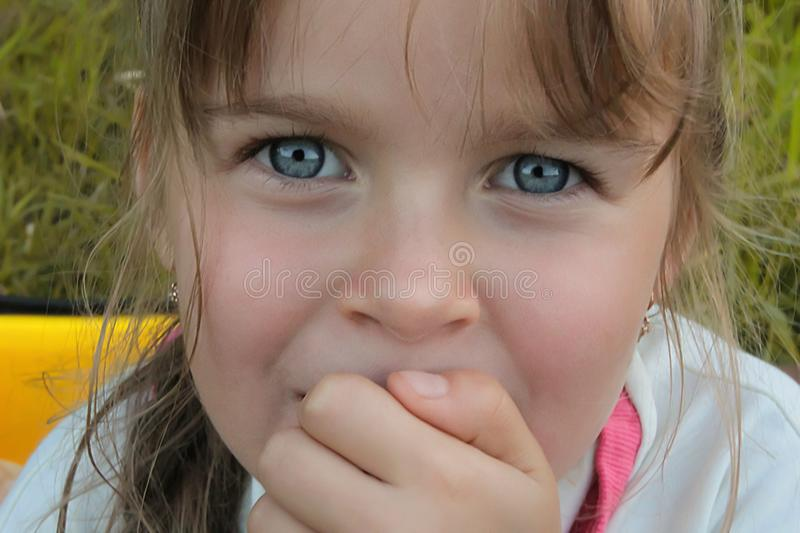 A cute European/Caucasian little girl with big with blue expressive eyes looking directly into the camera. Close-up stock photography