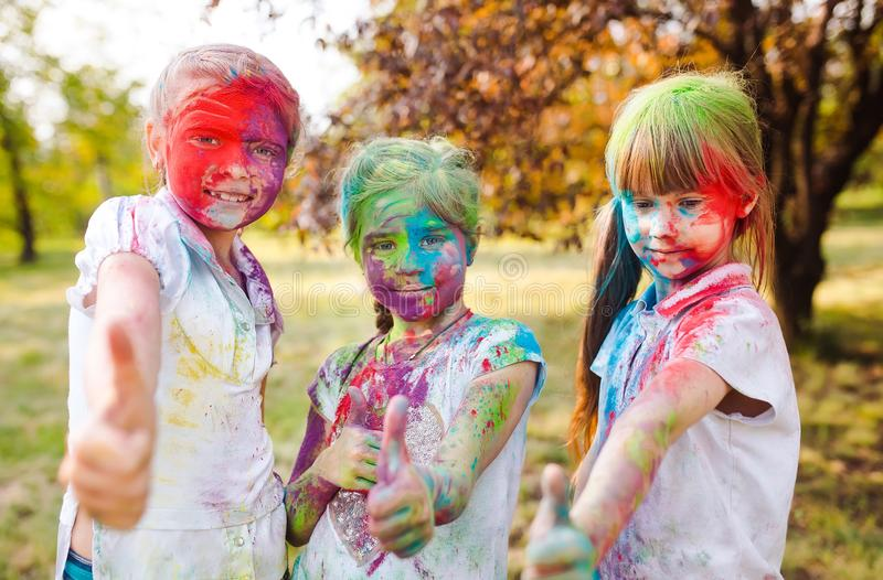 Cute european child girls celebrate Indian holi festival with colorful paint powder on faces and body royalty free stock photography