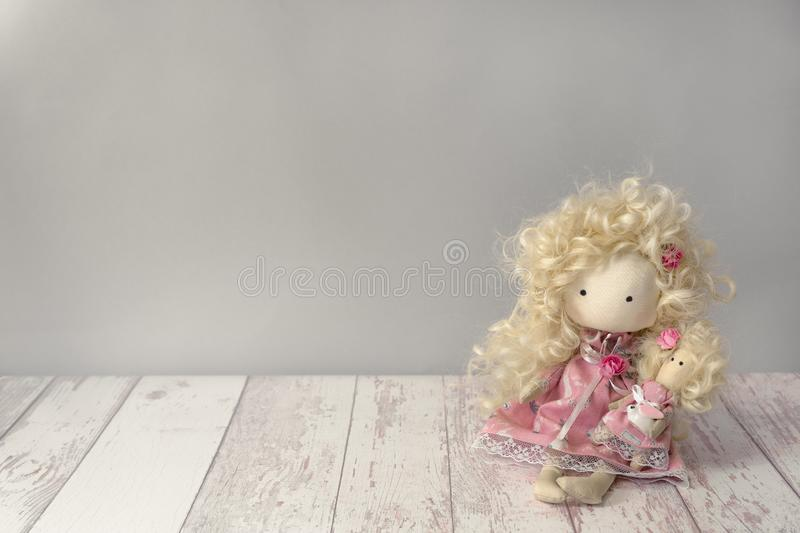 Cute fabric doll girl in pink dress with white rabbit sits on a white wooden table with copyspace stock images