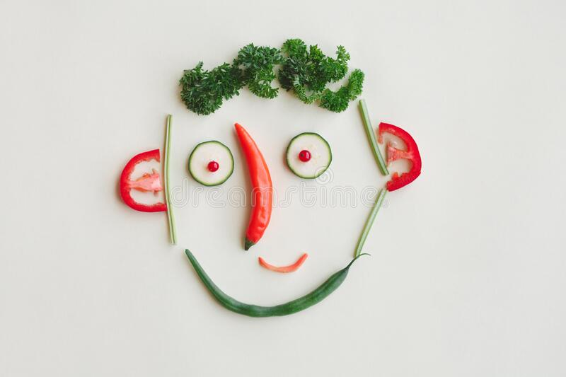 cute face made of vegetables, berries and greenery, parsley, zucchini, sweet pepper, asparagus stock photo
