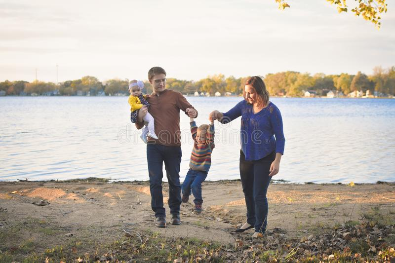 Cute Family by Lake. A cute family with a mom, dad, little boy and little baby girl, playing together by the lake in the fall. Family of four. American Dream stock photography