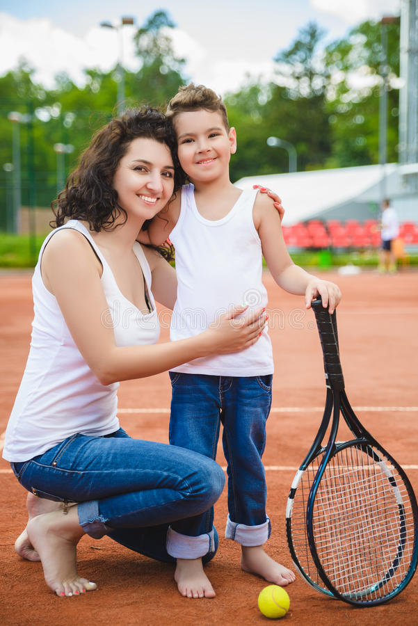 Cute family or mother and son playing tennis and posing in court outdoor royalty free stock photography