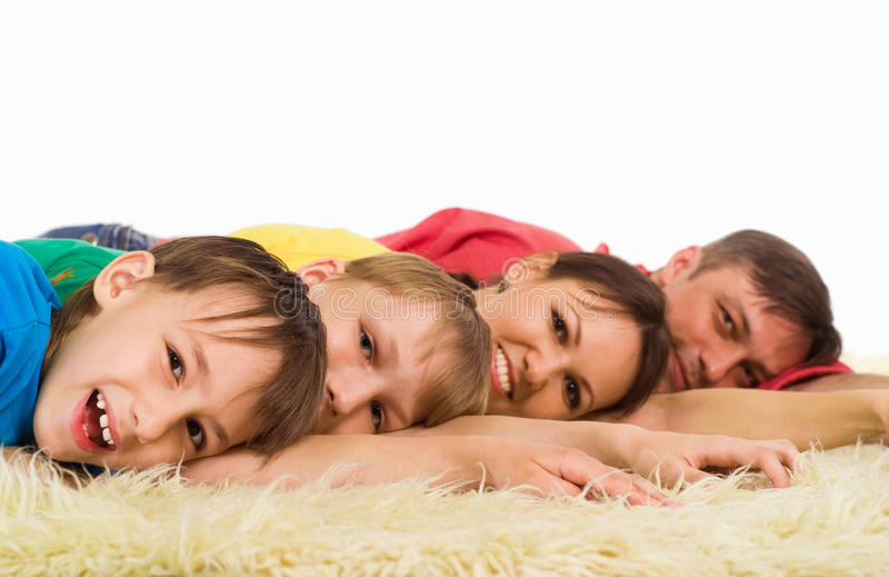 Cute family portrait. Cute family lying on a carpet on white stock photos