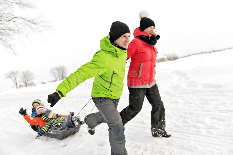 Cute Family Pulling Sledge Through Snowy Landscape royalty free stock photography