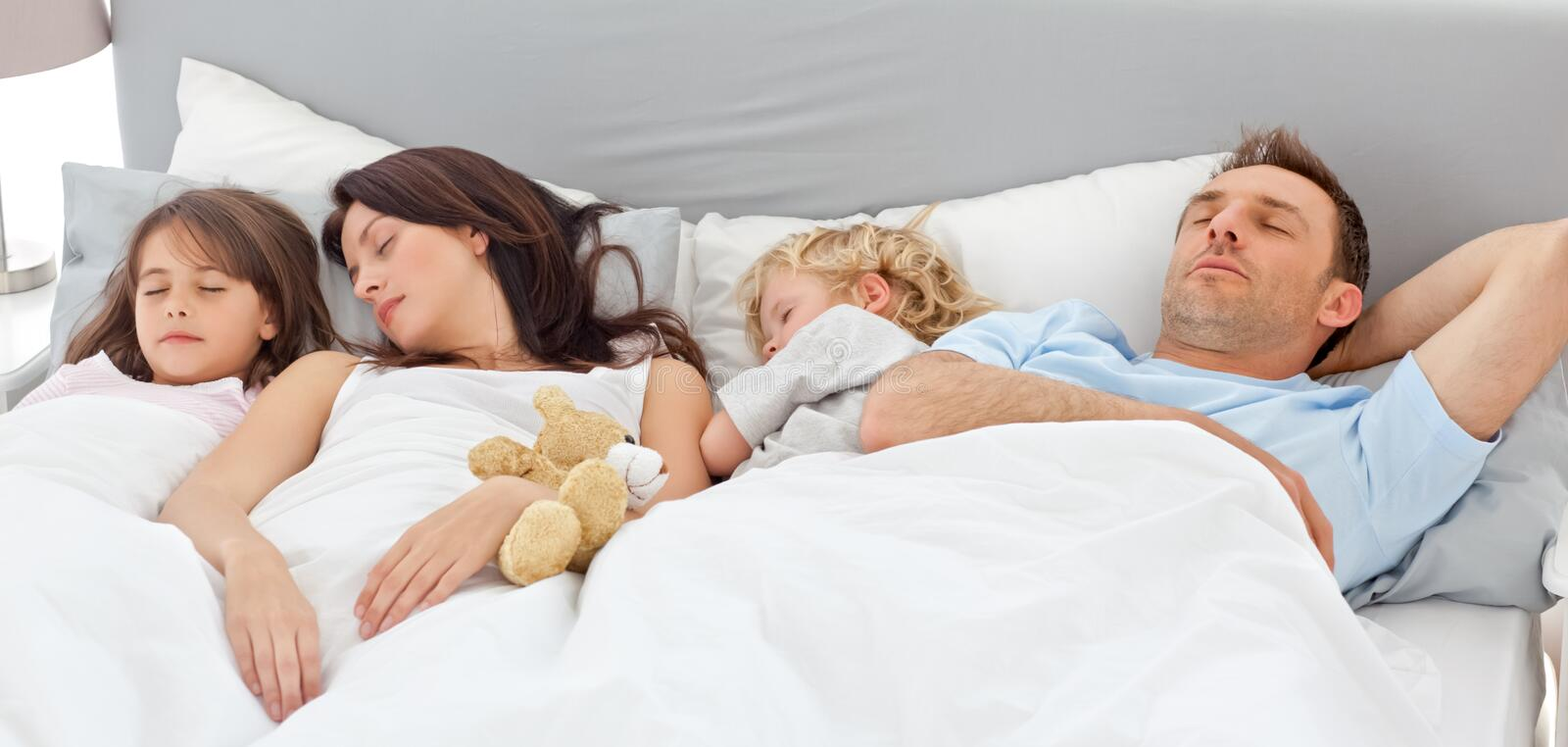 Cute family sleeping together. In the parents's bed stock image
