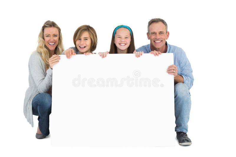 Cute family smiling at camera holding poster. On white background stock photography