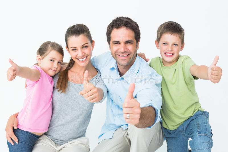 Cute family smiling at camera together showing thumbs up. On white background royalty free stock image