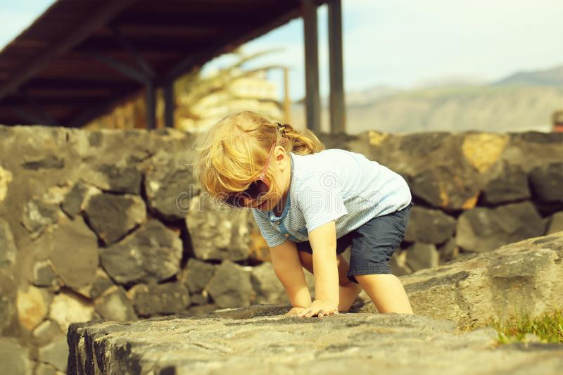 Cute fashionable baby boy in sunglasses. With blond hair in blue tshirt and shorts climbs on stone wall on sunny summer day on natural background stock photos