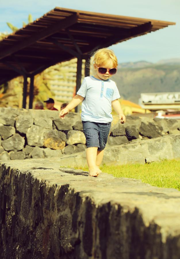 Cute fashionable baby boy in sunglasses. With blond hair in blue tshirt and shorts walks barefoot on stone wall on sunny summer day on natural background stock image